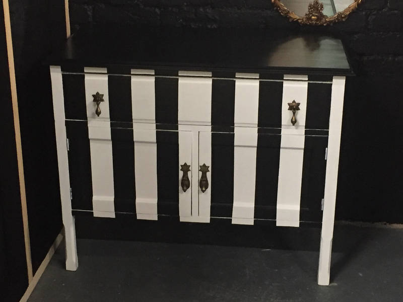 Black And White Striped Side Board With Raspberry Red Interior With Gold Door Knobs